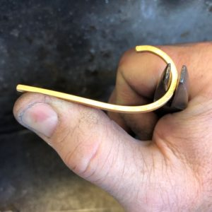 plain gold wedding band being shaped